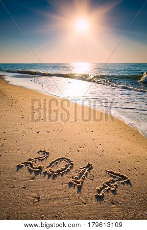 Year 2017 written at the sand on a sea beach. Majestic sunrise.