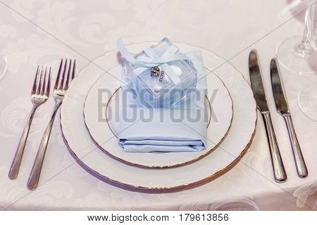 luxury wedding reception. stylish glasses plates on napkins and silver cutlery and gifts for guest on round table at expensive catering. space for text. decor for feast at holidays