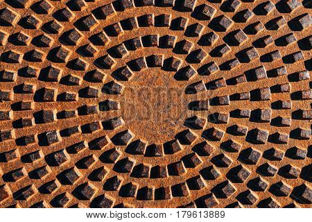 Concentric pattern on corroded manhole cover top view of abstract metal texture