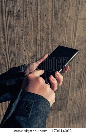 Close up of authentic female hands on the street using mobile phone to send text message