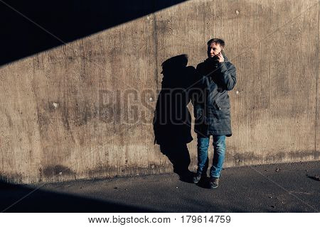 Serious authentic woman with short hair talking on mobile phone on the street in the under passage winter setting sun casting contrastly shadows on the wall