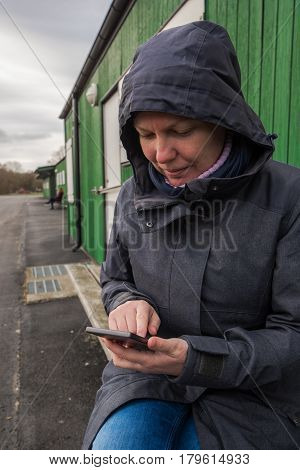 Authentic woman in winter jacket using mobile phone to type sms message outdoors while sitting on the bench on a cold day