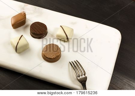 A photo of various artisan chocolate bonbons with a small dessert fork and copy space