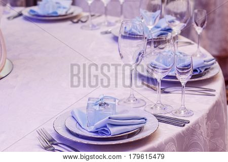 Luxury Wedding Arrangement Of Stylish Glasses Plates On Napkins And Silver Cutlery On Round Table At