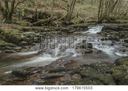 Stunning Waterfall Landscape In Cross Over Between Autumn And Winter With Fall Colour