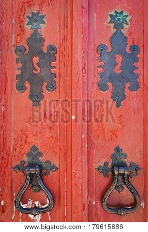 Detail of an old red wooden doors with black ironmongery