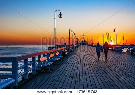 Sunrise at the wooden pier (molo) in Sopot Poland and a unrecognizable walking couple