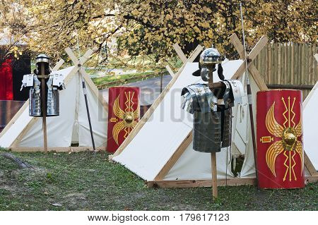 Military metal uniforms of the ancient Roman warriors near their campaign tents in a forest park
