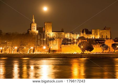 Nighttime panorama of historic Avignon with rising moon, Provence