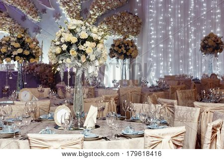 Luxury Wedding Decor With Flowers And Glass Vases With Jewels On Round Tables. Arrangements Of Decor