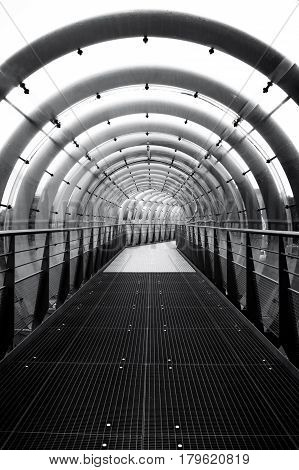 Futuristic abstract glass and steal tunnel receding into the distance. Black and white