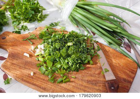 Green herbs. Freshly chopped parsley dill and green onions.