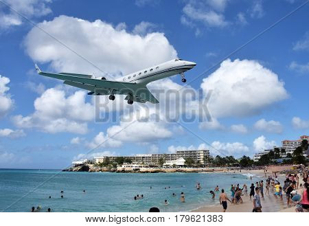 MAHO BEACH - ST MAARTEN: Jet lands low over the beach in St Maarten in the Caribbean on December 24 2015 as tourists enjoy the landmark location