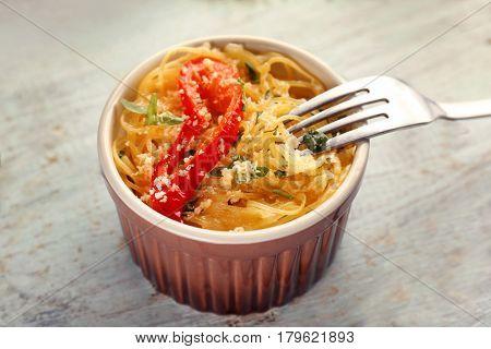 Delicious spaghetti in ramekin on wooden table