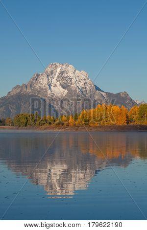 a scenic reflection of the Teton range in autumn