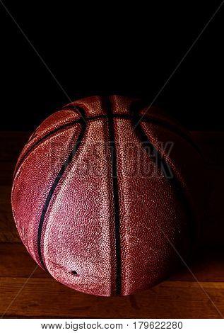 Basketball on a gym floor over black