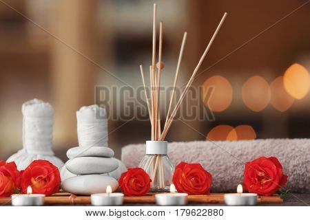 Beautiful spa composition with reed freshener and candles on blurred background
