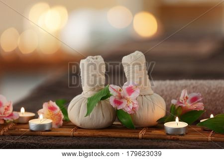 Beautiful spa composition with massage compress balls and candles on blurred background