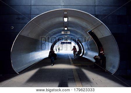 Persons run through an modern oval underpass. Daylight, hard shadow