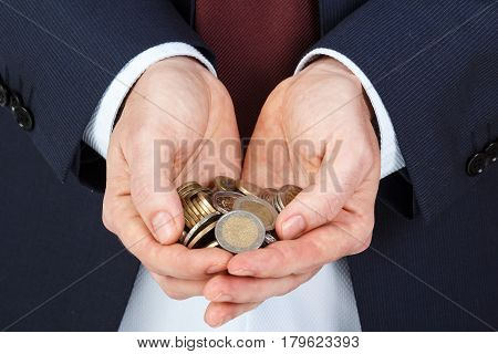 Businessman hands holding a pile of euro coins. Business concept.