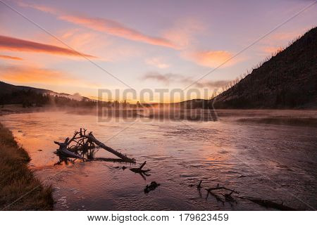 a colorful sunrise on the Madison River in Yellowstone National Park