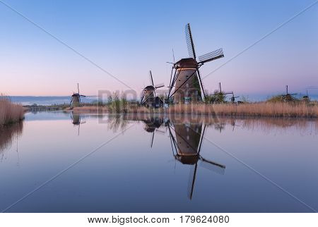Windmills And Clear Blue Sky At Sunrise In Kinderdijk, Netherlands