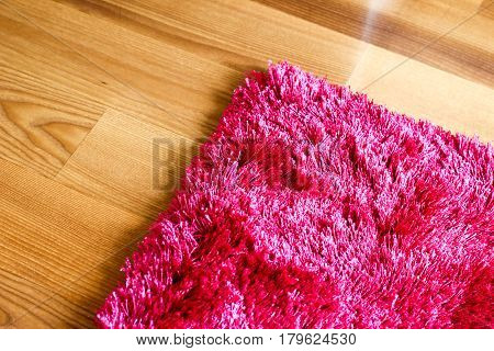 Pink Purple Rug On Wooden Floor Cropped Detail