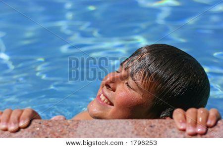 Young Boy Enjoying The Sun In A Swimming Pool