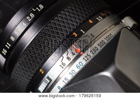 Old film camera lens with depth of field scale and focus ring