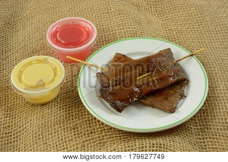Chinese food appetizer of beef skewers in spicy sauce with small containers of sweet and sour sauce and mustard sauce
