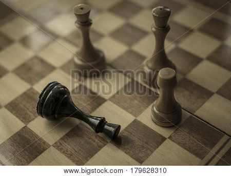 Chess game. Black king is checkmated and fallen on chessboard. game over. Old wooden chess