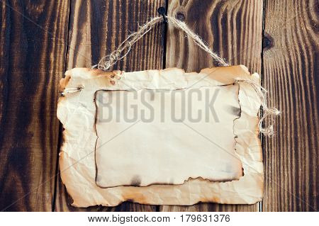 scorched paper hanging on a rope on a wooden brown background