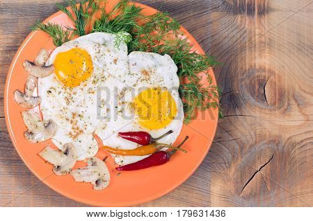 Fried two eggs with champignons, dill and red chili pepper on an orange plate on a wooden background