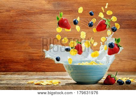 Healthy breakfast with milk flying corn flakes strawberries and blueberries.
