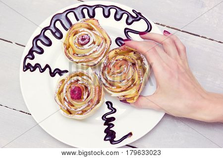 woman's hand take one of three apple muffins with raspberries in the center, drizzled with chocolate sauce leaving a zigzag trail on a white plate on a wooden grey background