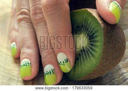 Kiwi and skin care of a beauty female hand with green and white moon nail art manicure on a wooden background