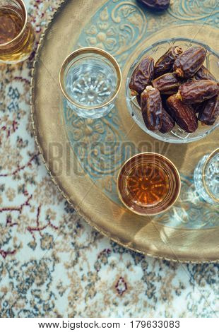Middle eastern ritual of drinking black tea called Suleimani Tea, with date fruits. Top view of tea served in traditional cups in an ornamental tray.