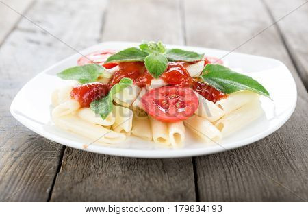 Pasta with vegetables on a wooden table