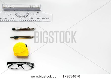 architect working desk with glasses, compass, tape-line and ruler on white background top view mock up