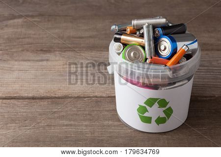 battery recycle bin with old element on wood table