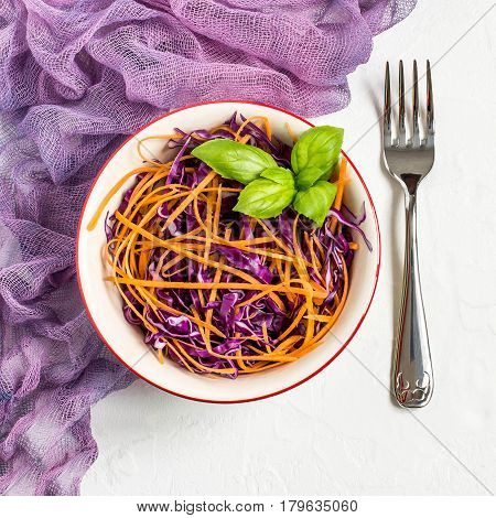 Fresh vitamin salad of red cabbage (scotch kale) with carrot and basil on white textured background. It is used in dietary and vegetarian food. Square image
