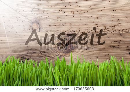 German Text Auszeit Means Downtime. Spring Season Greeting Card. Bright, Sunny And Aged Wooden Background With Gras.