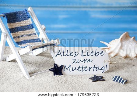 Summer Label With German Text Alles Liebe Zum Muttertag Means Happy Mothers Day. Blue Wooden Background. Card With Holiday Greetings. Beach Vacation Symbolized By Sand, Deck Chair And Shell.