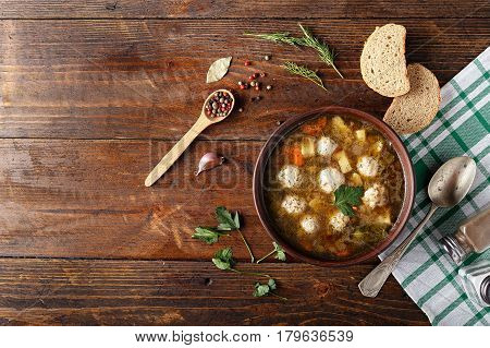 Soup with meatballs in a clay plate. Next to the plate is a napkin bread and spices space for text