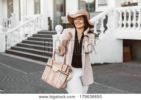 Young stylish woman wearing neutral blazer and hat with handbag walking on the city street in spring. Casual fashion, elegant look. Plus size model.