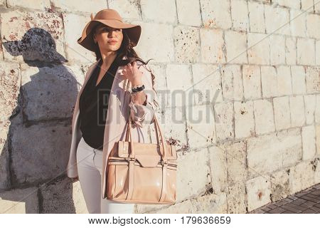 Young stylish woman wearing neutral blazer, hat and handbag walking on the city street in spring. Casual fashion, elegant look. Plus size model.