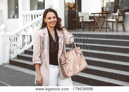 Young stylish woman wearing neutral blazer with handbag walking on the city street in spring. Casual fashion, elegant look. Plus size model.