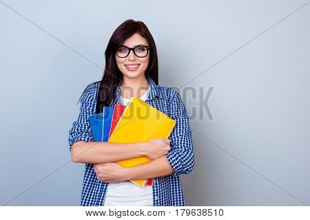 Smart Beautiful Woman In Checkered Shirt And Spectacles Holding Copybooks Against Gray Background
