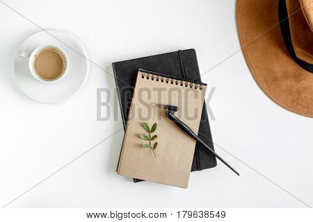 author office with hat and cup in professional writer concept on white work desk background top view