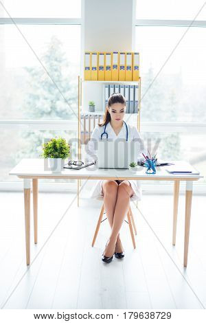 Front View Portrait Of Pretty Doctor Sitting At Her Medical Office And Searching Information In The